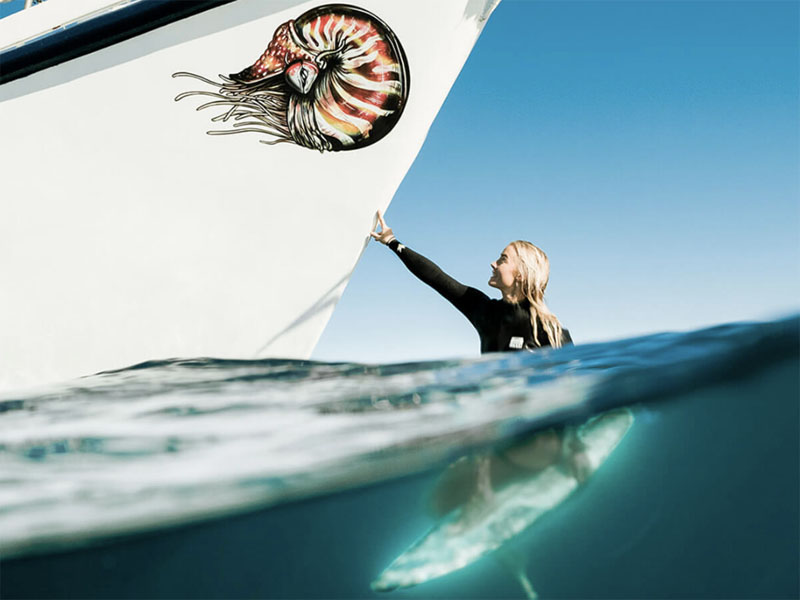 TROPIC ROVER girl on surfboard touching hull