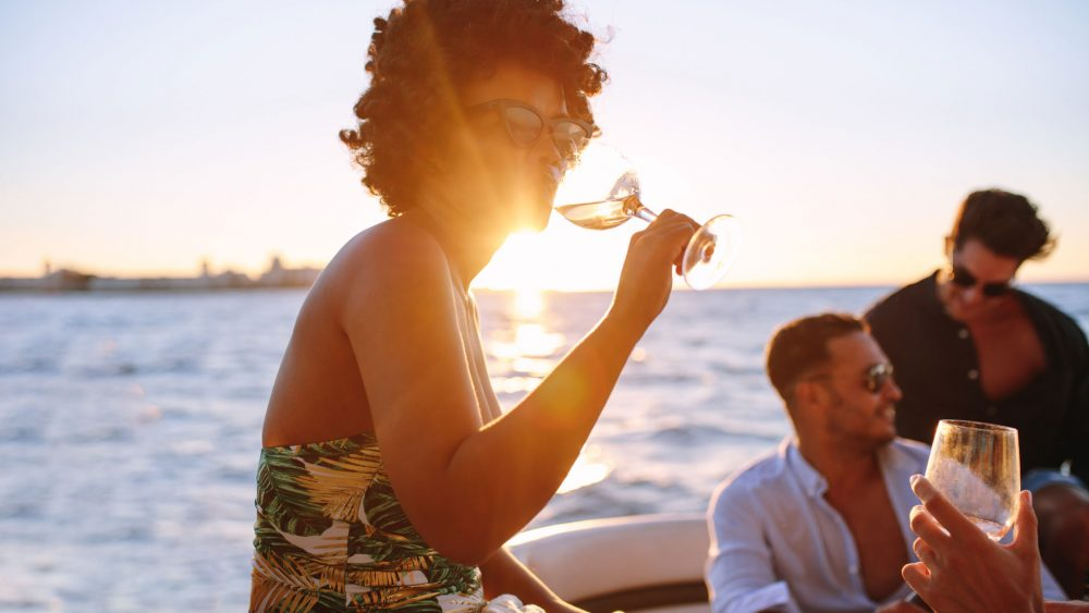 PiGLET boat charers woman-relaxing-drinking-wine-at-sunset